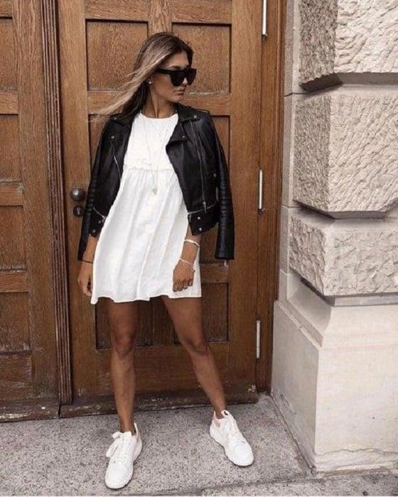 Chica usando chaqueta de cuero negra con vestido blanco y tenis del mismo color