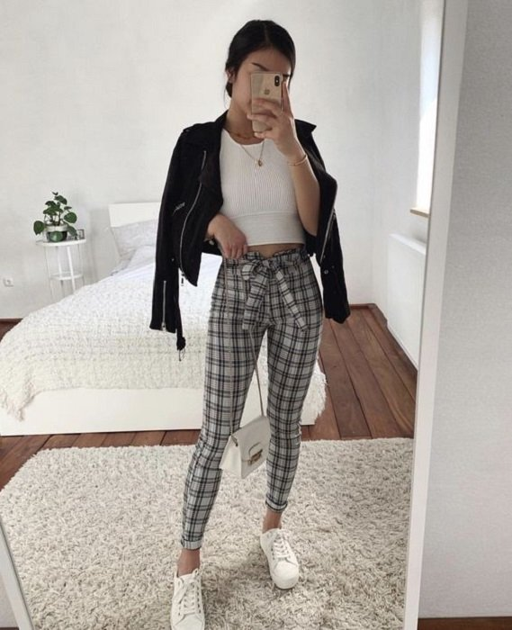 Girl wearing black leather jacket with plaid print pants and white blouse