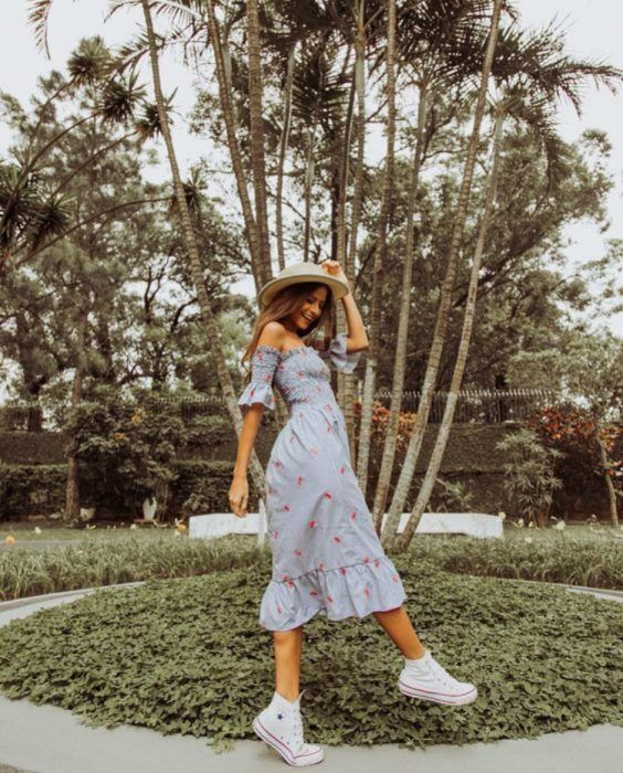 Girl wearing summer outfit of midi dress, off the shoulder, white tennis shoes, and straw hat
