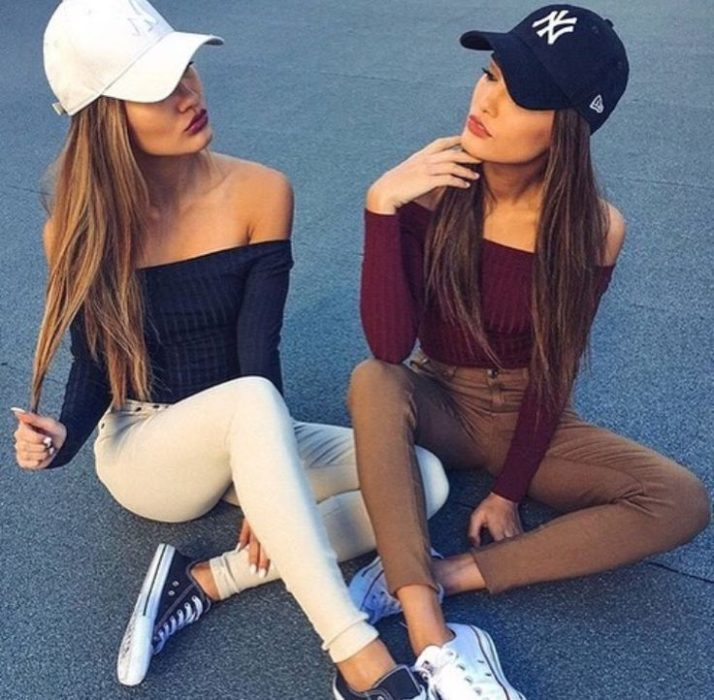 Chicas usando outfit similar y gorras
