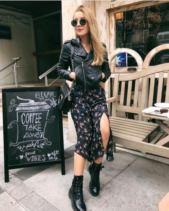Long loose hair blonde girl in dark sunglasses and long floral dress, a black leather jacket and dr. martens