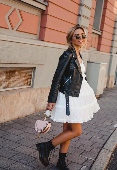 Loose long hair blonde girl in fluffy white dress, black leather black jacket and dr. black martens