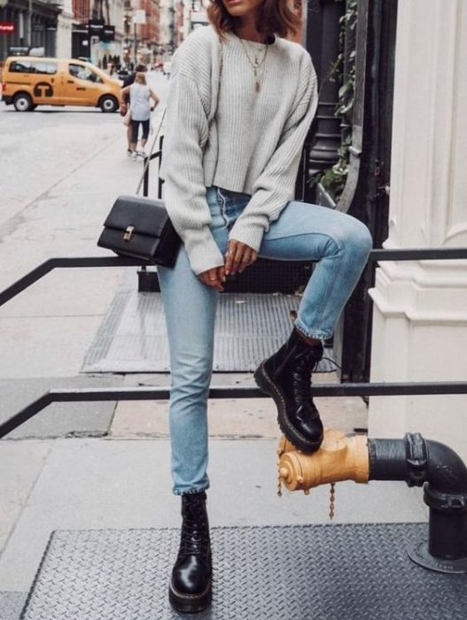 Girl sitting on railing in oversized gray sweater, blue jeans, square black shoulder bag and dr. black martens