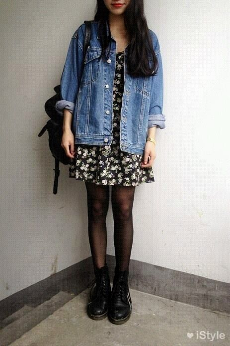 Brunette girl with lake and dark hair in short flowered dress and denim jacket wearing dr. martens