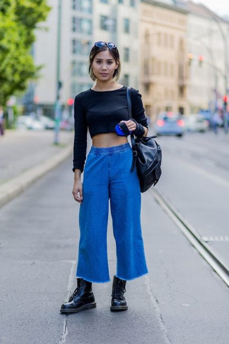 Asian slim girl in black long sleeve top and navy blue culottes with dr. martens