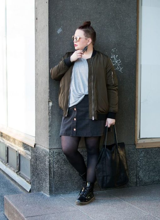 Plus size girl leaning against the wall with military green jacket, gray blouse, black skirt, black stockings and dr. martnes