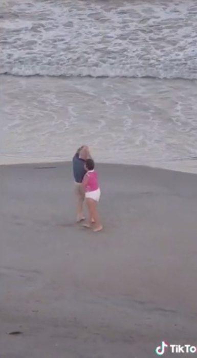 Pareja de ancianos baila alegremente en la playa