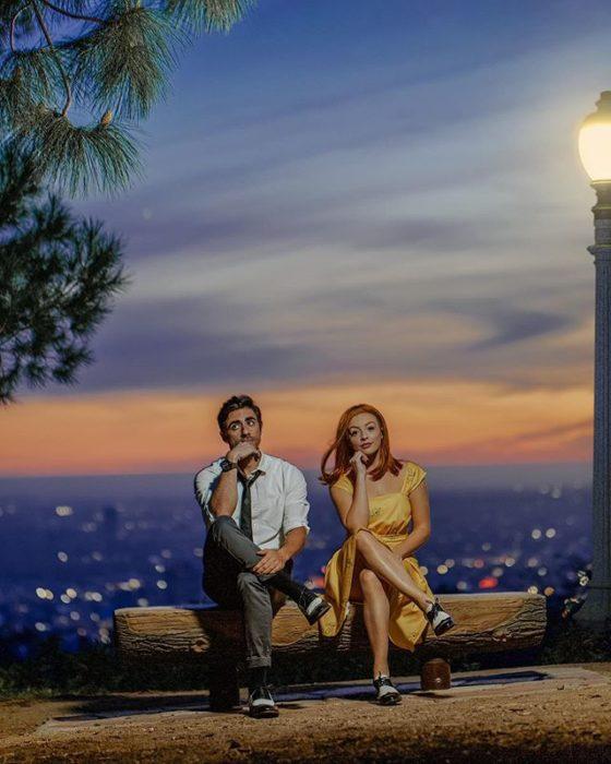 Pareja recreando escena de la película La la land, pareja sentada sobre un tronco mirando las estrellas