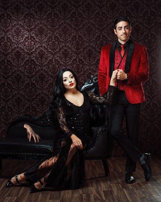 Pareja recreando escena de la película Los locos Addams, sostenidos de las manos y llevando ropa oscura