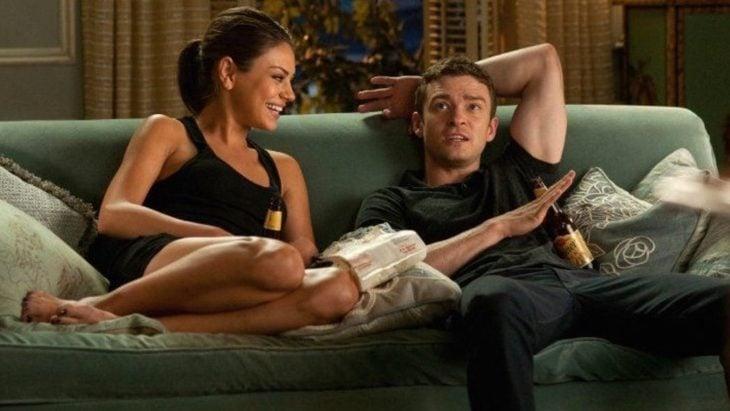 Mila Kunis y Justin Timberlake sentados en un sofá y bebiendo cerveza durante una escena de la película Amigos con beneficios