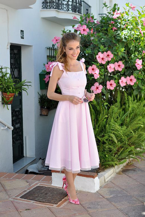 Girl in pastel pink dress from straps to bows
