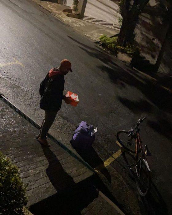 Repartidor sosteniendo una caja de de cartón con un par de tenis dentro