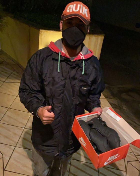 Repartidor sosteniendo una caja con un par de tenis negros dentro
