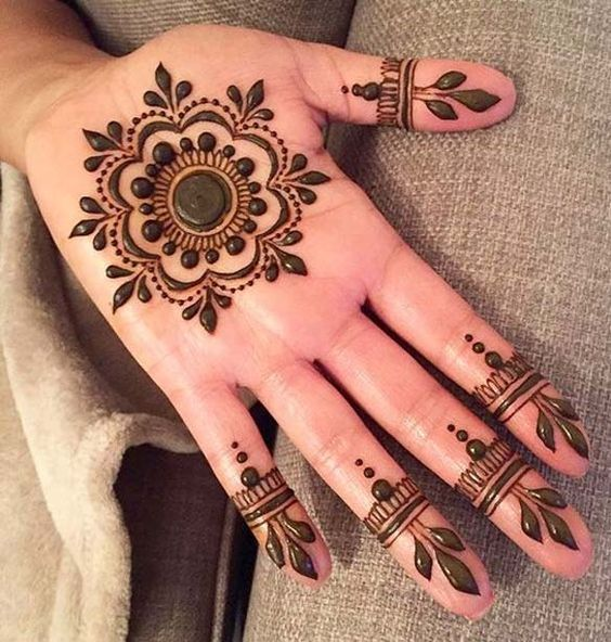 Henna tattoo in the shape of a flower on the palm of the hand