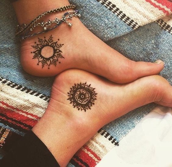 Sun and moon henna tattoos on feet