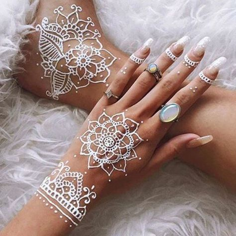 White henna tattoo on right hand with long transparent nails