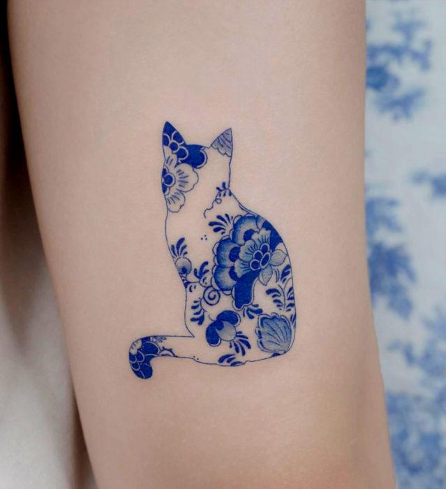 Tatuaje pequeño estilo japonés de tinta azul en el brazo; silueta de gato con flores dentro