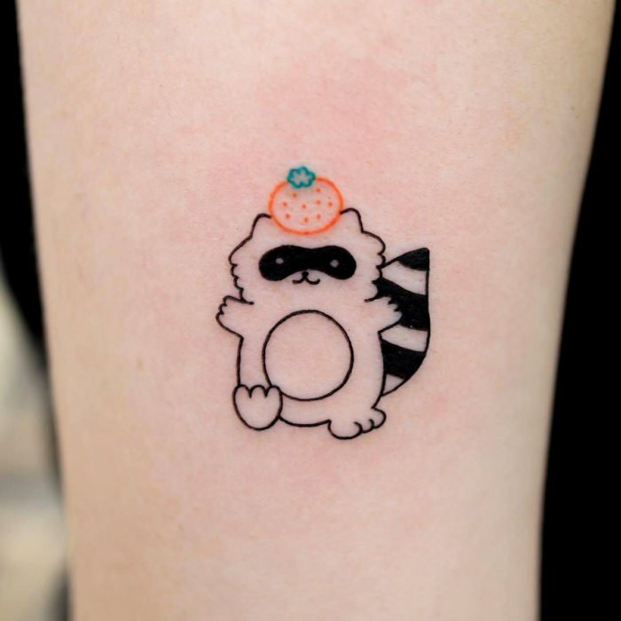 Cute kawaii tattoo on arm, raccoon with orange