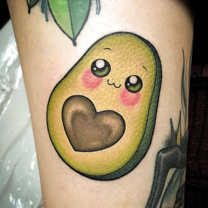 Tender kawaii tattoo on arm of cute avocado with happy face and seed in the shape of a heart