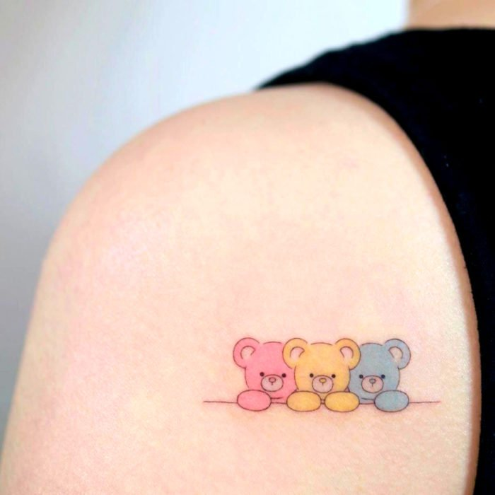 Cute kawaii tattoo on shoulder, teddy bears in pink, yellow and blue colors