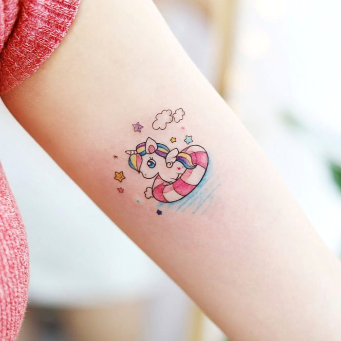 Cute little cute kawaii unicorn in pink float tattoo on arm