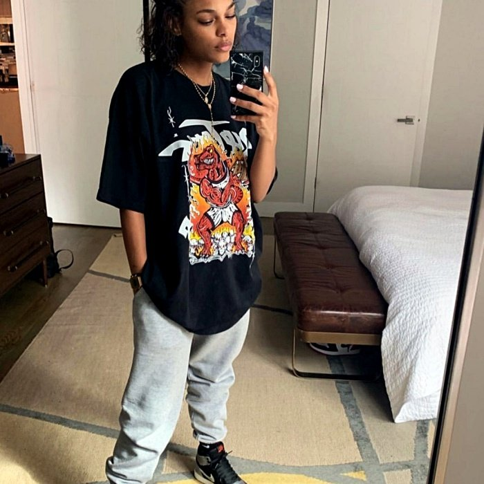 chica morena con camiseta oversized negra con estampado, pantalones grises deportivos y tenis negros