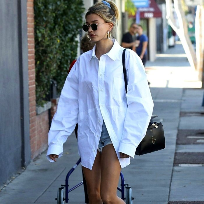 Hailey Bieber wearing an overisized white button down shirt, denim shorts, and sunglasses