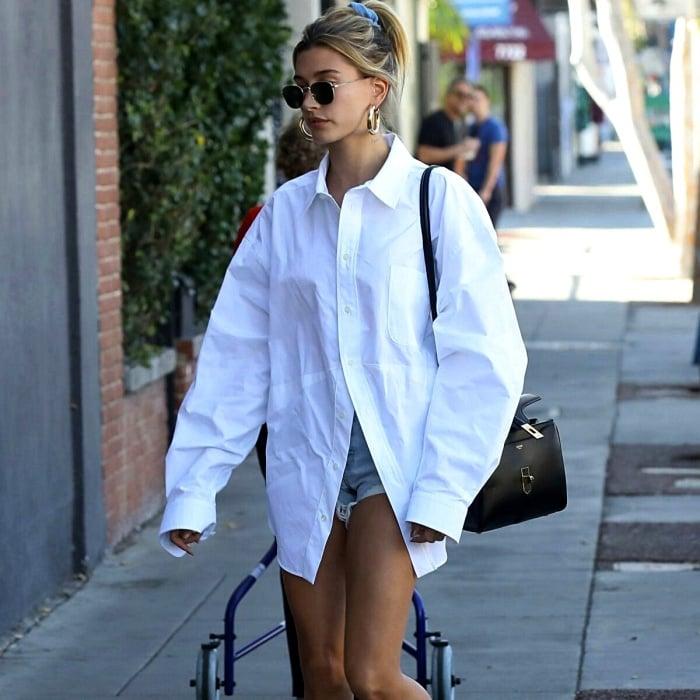 hailey bieber usando una camisa de botones blanca overisized, shorts de mezclilla y lentes de sol