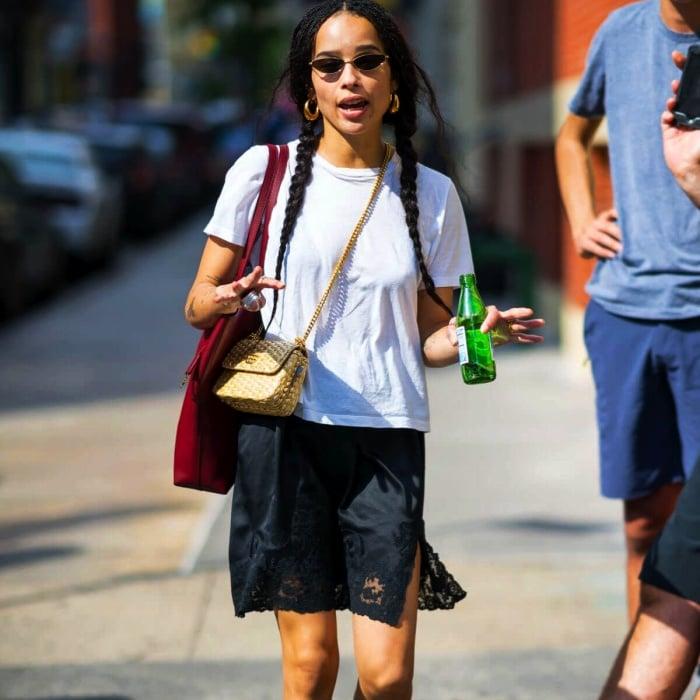zoe kravitz usando una camiseta blanca, falda azul, bolso de mano de paja y lentes de sol