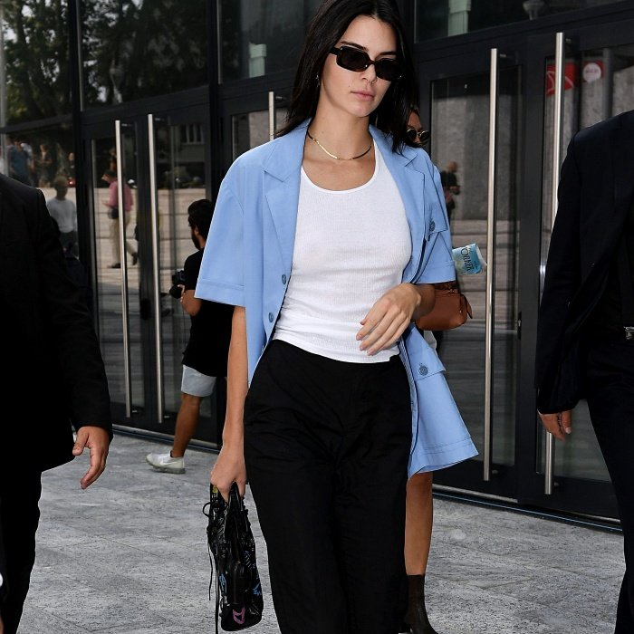kendall jenner wearing a blue button down shirt, white top underneath, black pants and dark sunglasses