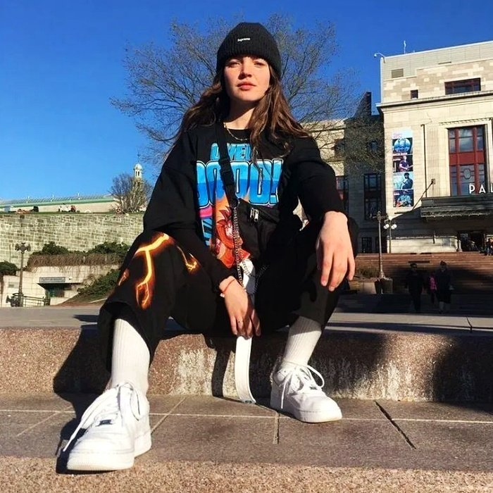girl with brown hair wearing a black beanie, black oversized t-shirt with blue letters, black pants with flames and white tennis shoes