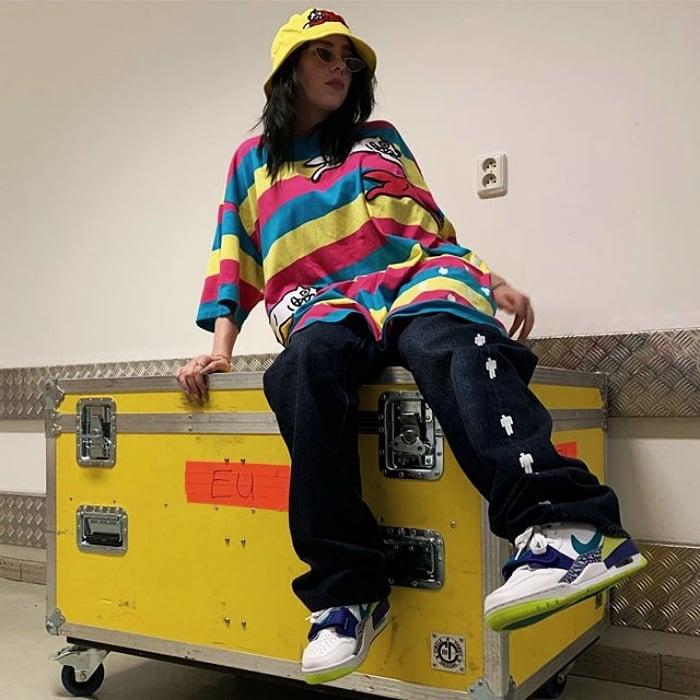 billie eilish con bucket hat amarillo, camisa oversized de rayas multicolor, pantalones cargo negros y tenis deportivos blancos