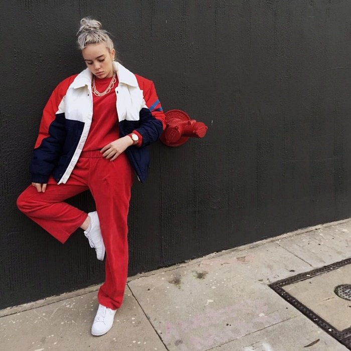 billie eilish wearing a baggy bomber jacket with a red top, red pants and white sneakers