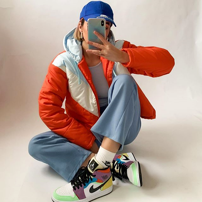 girl wearing blue cap, orange jacket, blue pants and multi-colored sneakers