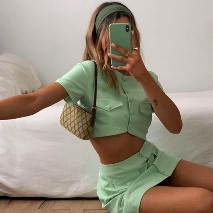girl wearing mint color outfit, with crop top shirt, miniskirt and brown and beige handbag