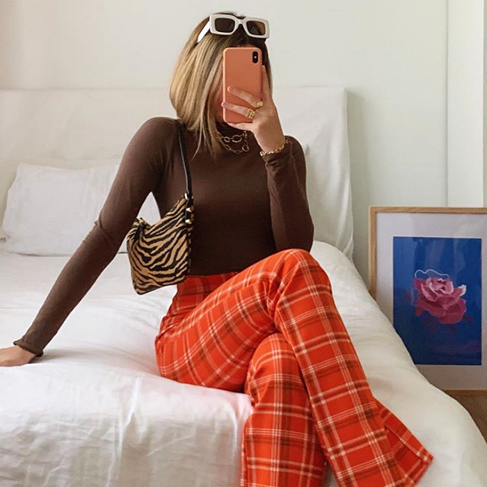 girl wearing long sleeve brown top, orange flared pants and small tote bag