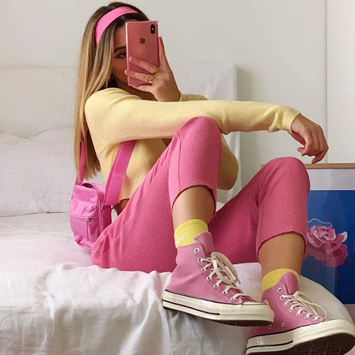girl wearing yellow long sleeve top, pink pants, yellow socks, pink converse and small pink tote bag