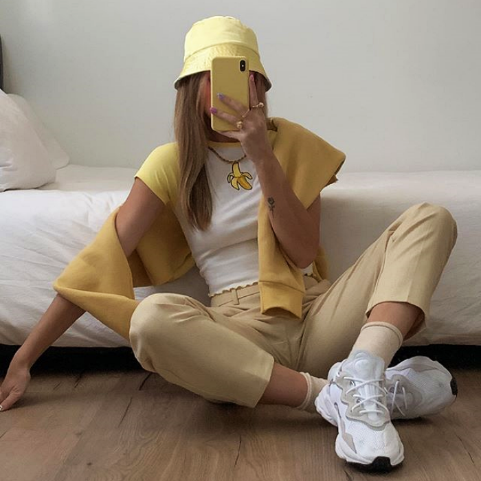 girl wearing yellow set, bucket-hat, white shirt, yellow shorts, white tennis shoes and yellow sweater