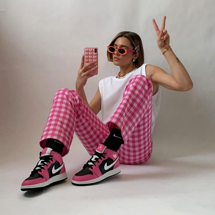 girl wearing sunglasses, white top, pink plaid pants, pink sneakers with black and white views