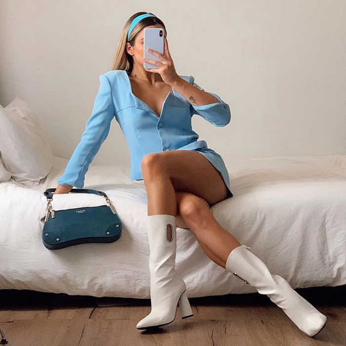 girl wearing blue headband, light blue outfit with jacket and skirt, white leather boots and blue handbag