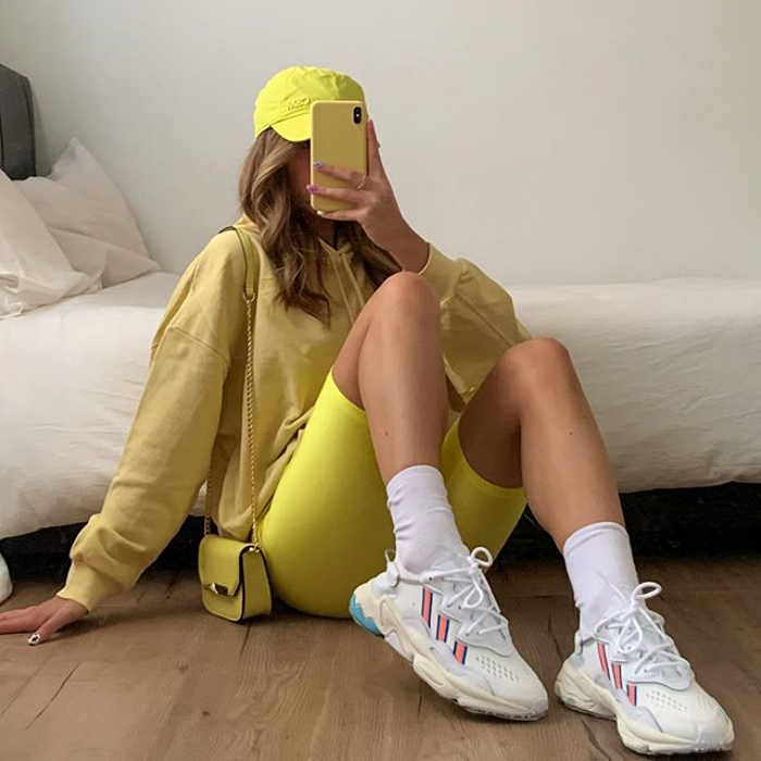 girl wearing yellow cap, yellow sweatshirt, yellow cycling shorts and white tennis shoes with long socks