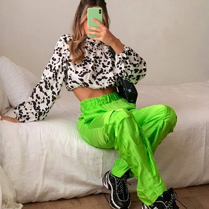 girl wearing white blouse with black, neon green pants and black tennis shoes