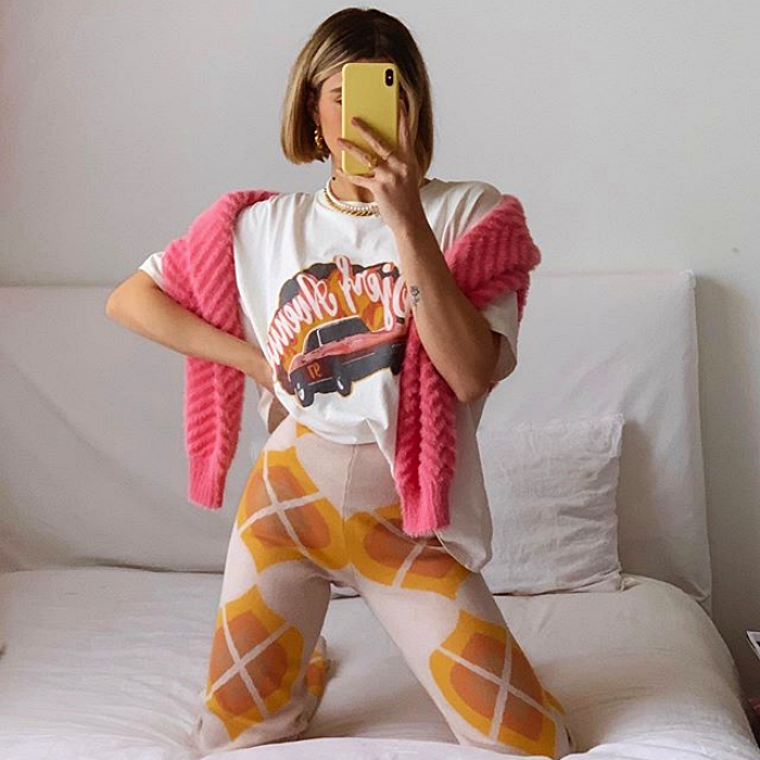 girl wearing white t-shirt with pink sweater print, cream pants with orange print