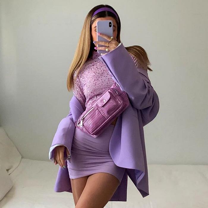 chica usando top morado con saco morado, falda morada y bolso de mano color fucsia