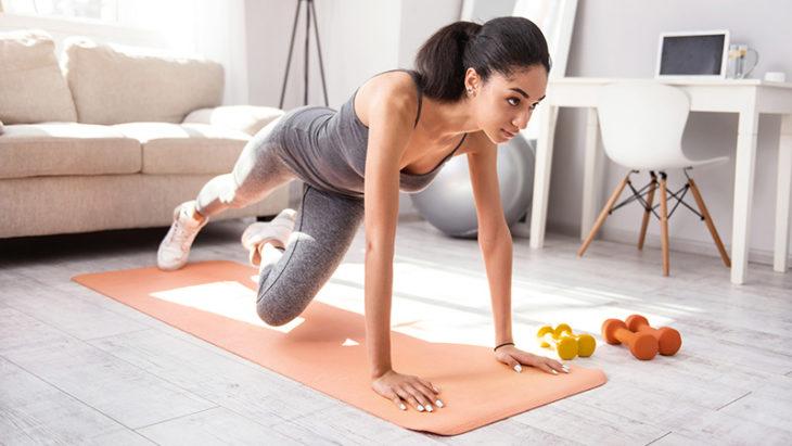 Chica morena haciendo ejercicio en tapete naranja