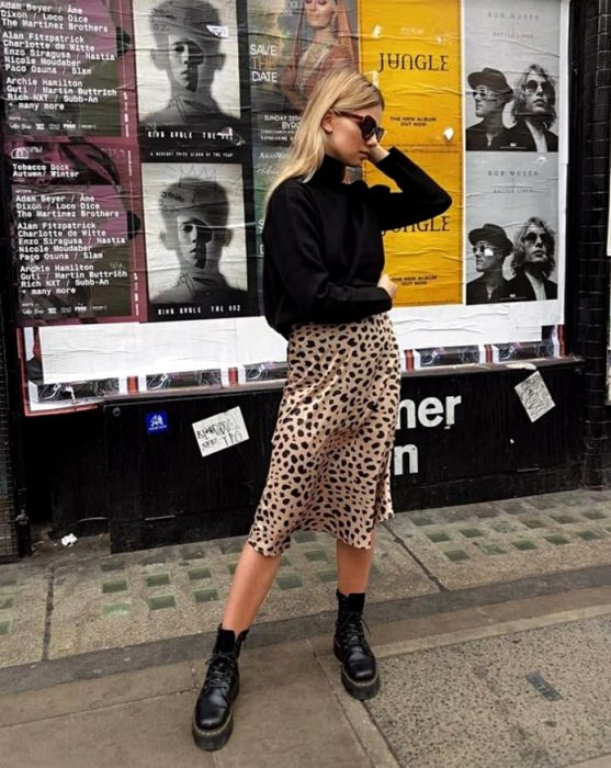 blonde girl wearing sunglasses, black turtleneck sweater, animal print satin slip dress and black leather boots