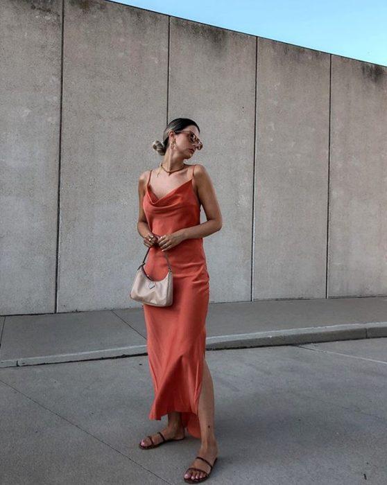 chica rubia con lentes de sol usando un vestido anaranjado de satén slip dress con bolso de mano color beige y sandalias de piso