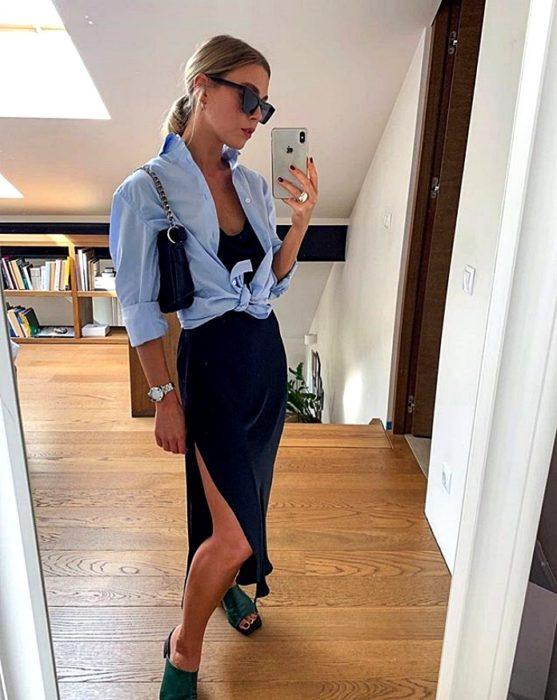 chica rubia con lentes de sol usando una camisa de botones azul con vestido de satén slip dress azul marino y sandalias de piso