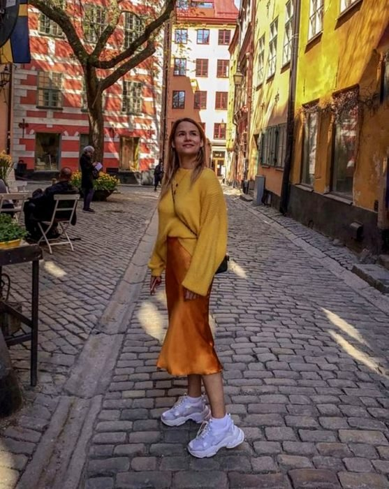chica rubia usando un suéter amarillo oversized, vestido de satén slip dress naranja con tenis deportivos blancos