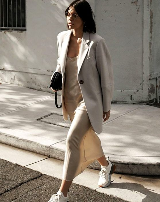 Long brown hair girl wearing light beige satin slip dress with white trainers, oversized blazer